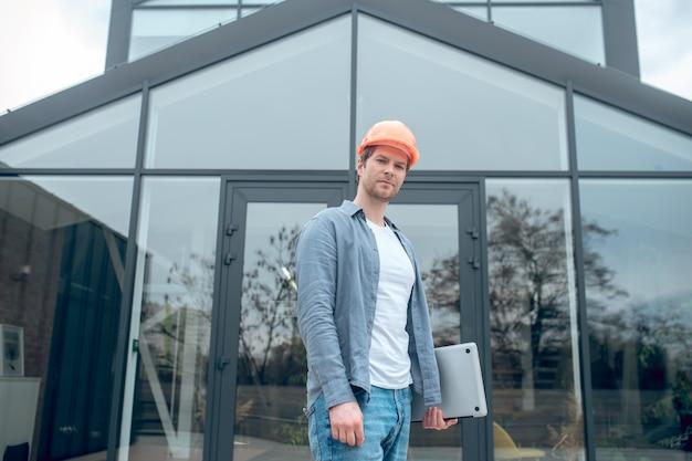 건물 근처에 노트북이 있는 보호용 헬멧을 쓴 남자