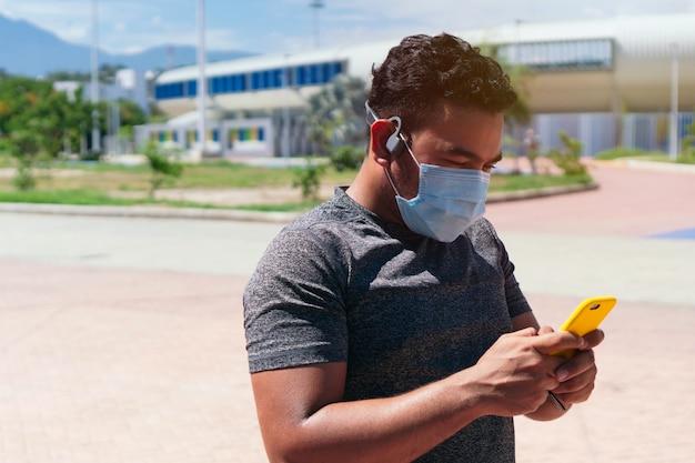 야외에서 훈련하는 동안 휴대 전화를 확인하는 보호 마스크를 쓴 남자