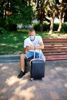保護マスクをかぶった男、スーツケースと携帯電話を持って屋外の公園のベンチに座って、コロナウイルスのパンデミック中の生活、空の旅、旅行のコンセプト。