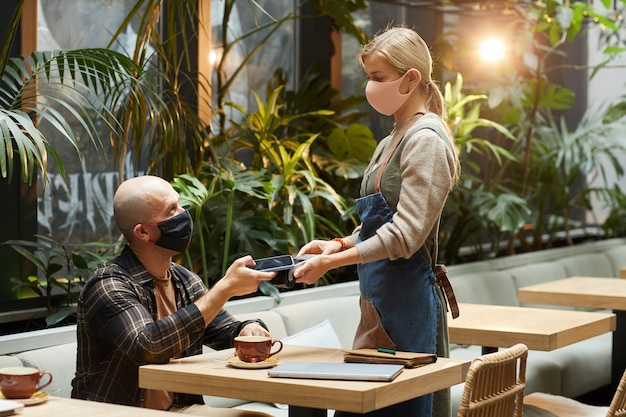 Мужчина в защитной маске использует свой мобильный телефон для оплаты заказа официанту во время пандемии в ресторане