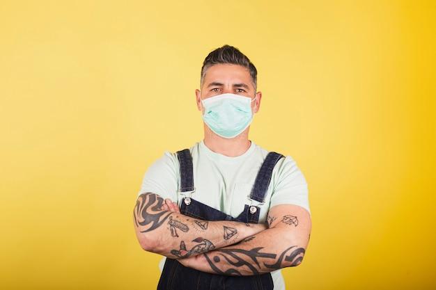 黄色の背景にデニムのオーバーオールと防護医療マスクの男。