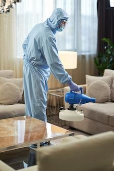 Мужчина в защитном комбинезоне и маске делает дезинфекцию, стоя в комнате. коронавирус и концепция карантина