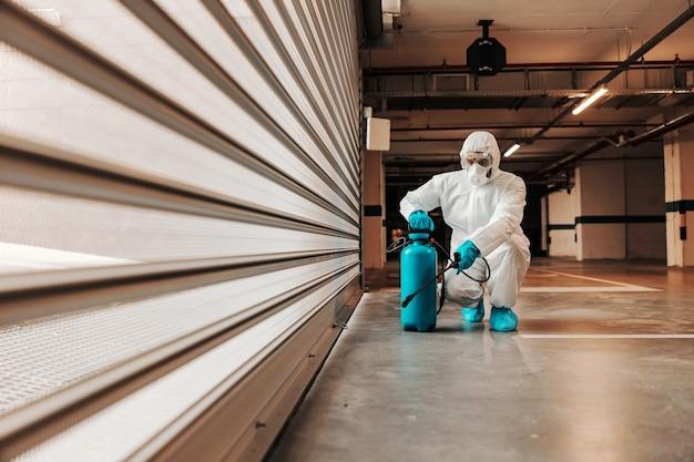 保護用の無菌の制服を着た男がしゃがみ、ガレージを消毒剤で消毒します。