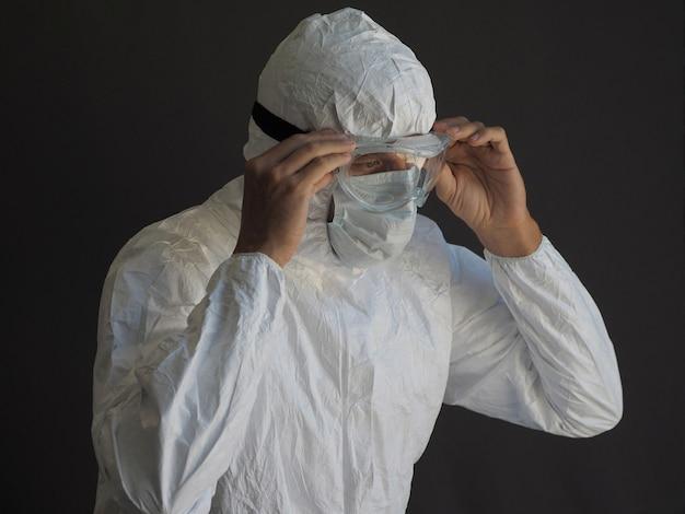 보호 복과 안면 마스크를 입은 남자가 고글을 착용합니다.