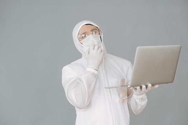 Человек в защитном костюме и очках на серой стене