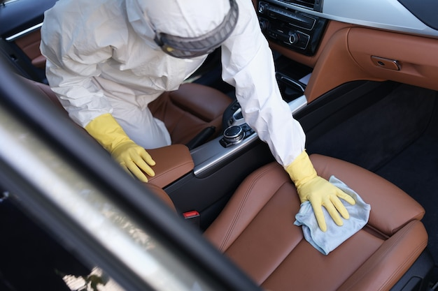 보호복을 입은 남자와 고무 장갑을 끼고 가죽 카시트를 소독제 클로즈업으로 닦는다
