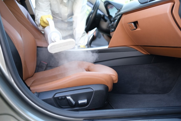 기선 근접 촬영으로 자동차 내부를 청소하는 보호복을 입은 남자