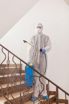 コロナウイルス汚染から建物を消毒する防護服を着た男。