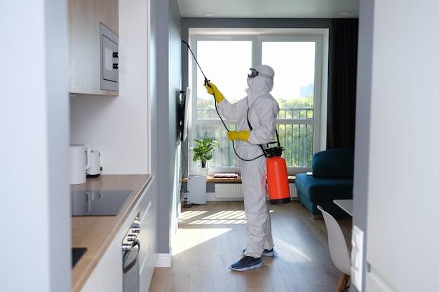 Человек в защитном костюме обрабатывает квартиру дезинфицирующим средством. как избавиться от плесени в квартире концепция