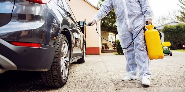 보호 복을 입은 남자는 자동차 타이어를 소독하고 코로나 바이러스 감염, 세균 또는 박테리아 오염을 예방합니다.