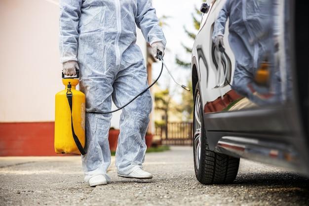 車のタイヤを消毒するマスクで防護服を着た男は、コロナウイルスの感染、細菌や細菌の汚染を防ぎます。