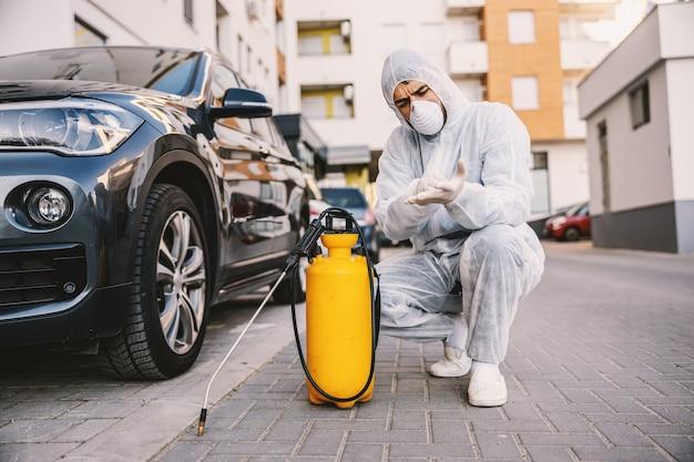 자동차 타이어를 소독하는 마스크가 달린 보호 복을 입은 남자는 covid-19 바이러스 코로나 바이러스 감염, 세균 또는 박테리아 오염을 예방합니다. 감염 예방 및 전염병 통제. 보호 수