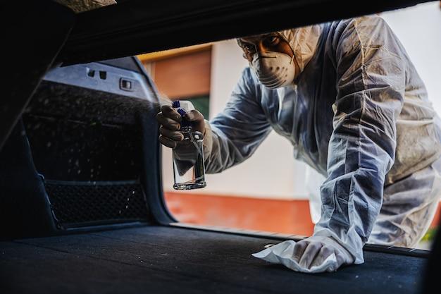 보호 복을 입은 남자는 차 안에서 마스크를 소독하고 자주 만지는 깨끗한 표면을 닦고 코로나 바이러스 감염, 세균 또는 박테리아 오염을 예방합니다. 감염