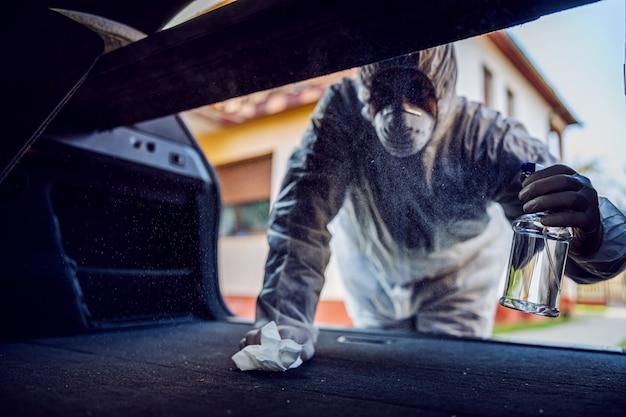 車内でマスクを消毒する防護服を着た男、頻繁に触れる清潔な表面を拭き取り、コロナウイルスの感染、細菌や細菌の汚染を防ぎます。感染