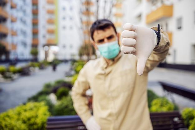 엄지 손가락, 바이러스 감염, 세균 또는 박테리아 오염을 보여주는 마스크가있는 보호 복을 입은 남자. 감염 예방 및 전염병 통제. Otective 한 벌 프리미엄 사진