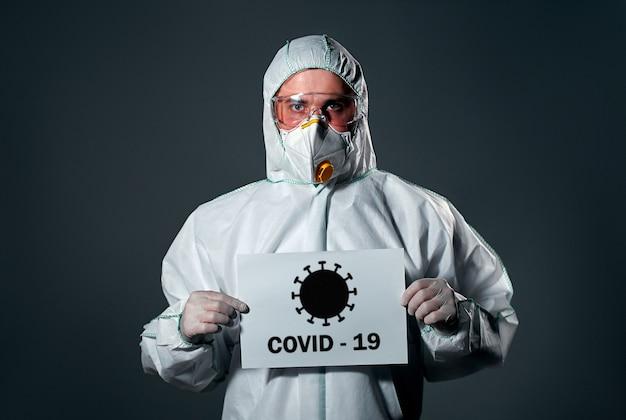 保護用の白いオーバーオールを着た男性、顔にマスクと眼鏡、紙、covid-19の碑文。