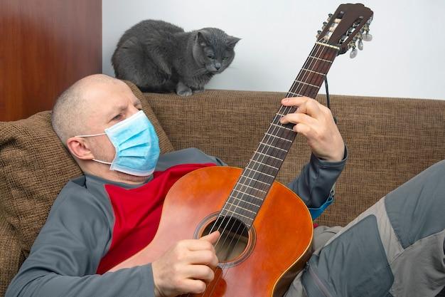 그의 얼굴에 의료 마스크를 들고 집에서 격리 된 남자는 소파에 누워 기타를 연주합니다. 코로나 바이러스가 유행하는 동안 휴식을 취하십시오.