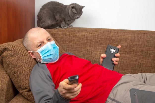 그의 얼굴에 의료 마스크로 집에서 격리 된 남자는 소파에 누워 tv를 본다