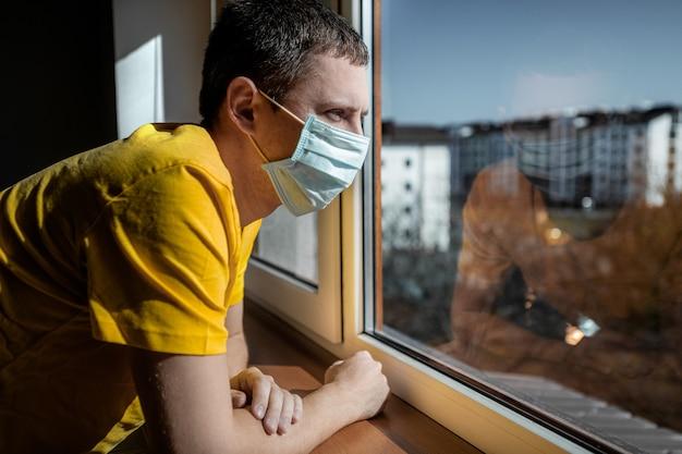 Человек на карантине из-за вируса сидит дома в маске и в солнечный день смотрит в окно. концепция коронавируса. covid-19