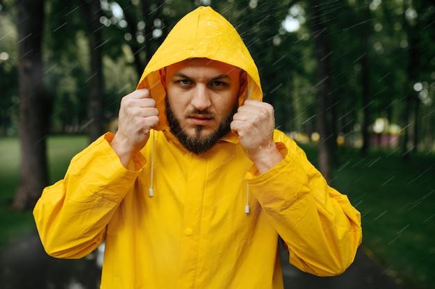 Человек в плаще надевает капюшон, летний парк в дождливый день. одинокий мужчина в плаще дождя на пешеходной дорожке, сырая погода в переулке