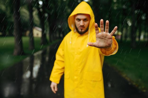 Человек в плаще протягивает руку, летний парк, дождливый день. одинокий мужчина в плаще дождя на пешеходной дорожке, сырая погода в переулке