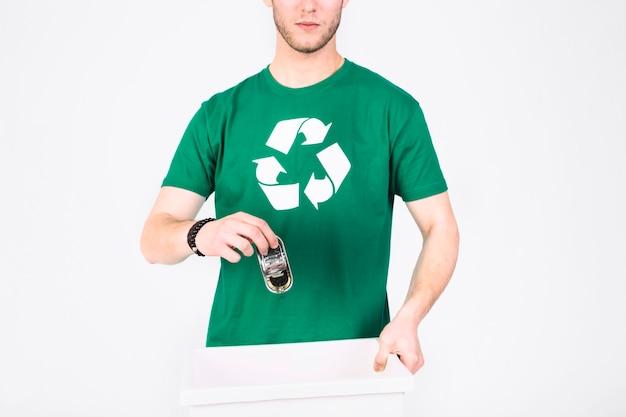 쓰레기통에 미니 주석 상자를 던지고 재활용 아이콘 티셔츠에 남자