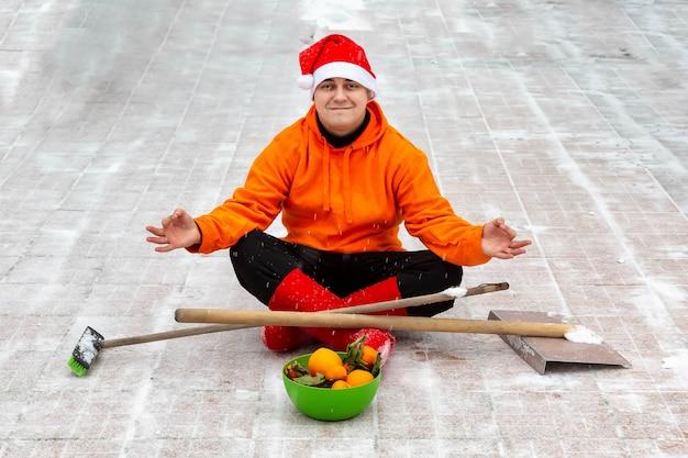 Человек в красной рождественской шапке и сапогах сидит в позе лотоса на территории своего двора с кистью и лопатой