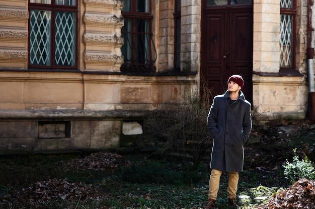 Человек в красной шляпе и сером пальто стоит перед старым домом