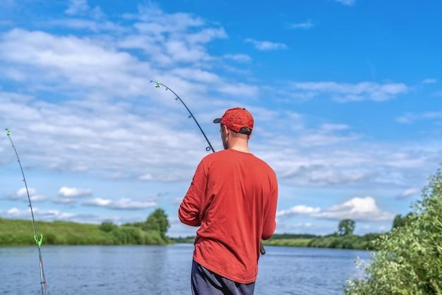 湖での赤い帽子釣りの男