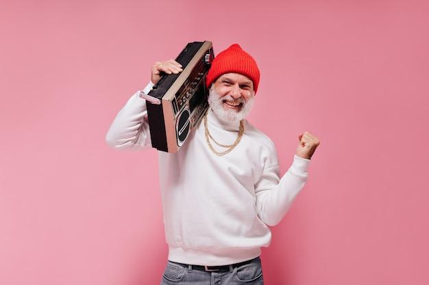ピンクの壁にレコードプレーヤーでポーズをとって赤い帽子の男