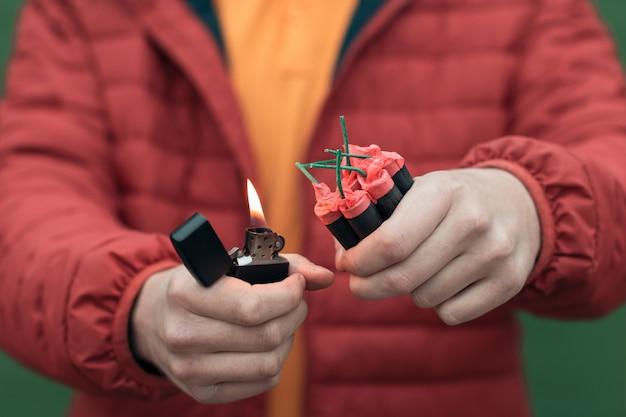 Мужчина в красном зажег несколько петард в руке с помощью бензиновой зажигалки.