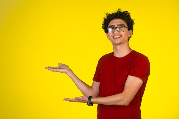 Человек в красной рубашке делает презентацию руками с радостью и весельем.
