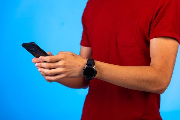 Человек в красной рубашке держит и болтает на смартфоне.