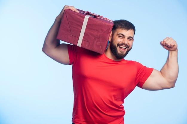 Мужчина в красной рубашке держит подарочную коробку на плече и показывает мышцы