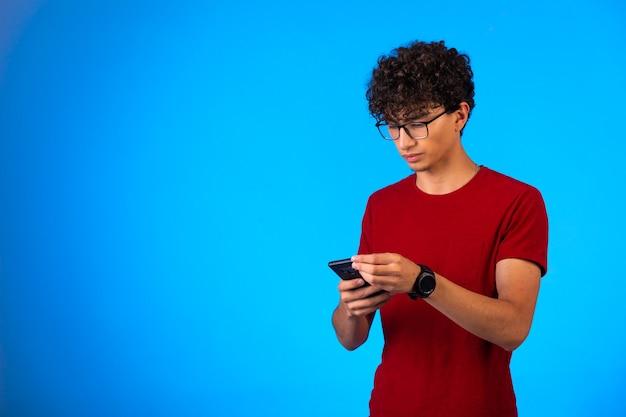 Selfieを取るか、電話をかける赤いシャツの男とタッチスクリーンのキーパッドを使用します。