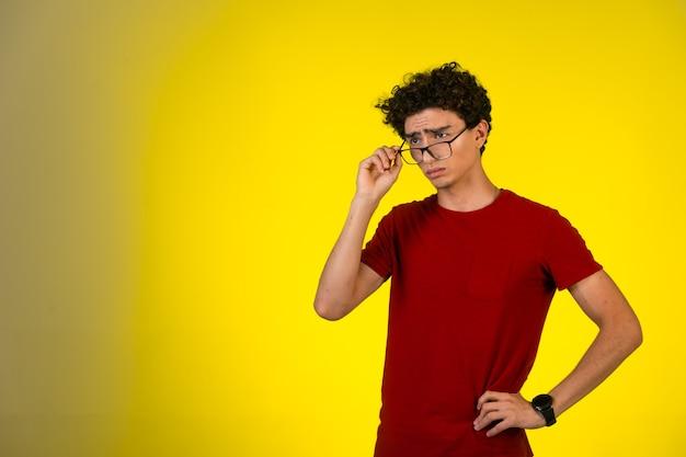 赤いシャツを着た男は眼鏡をかけ、混乱しているように見えます。