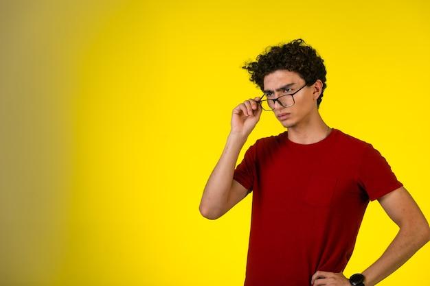 赤いシャツを着た男は眼鏡をかけ、失望しているように見えます。