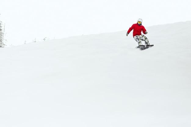 빨간 스키 재킷을 입은 남자가 그의 스노우 보드의 언덕을 내려갑니다.