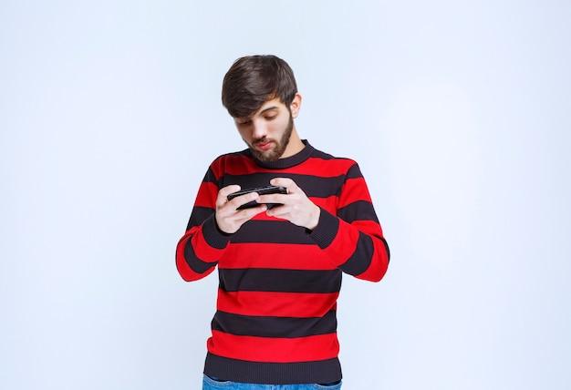 Человек в красной полосатой рубашке болтает или пишет текстовые сообщения на своем смартфоне.