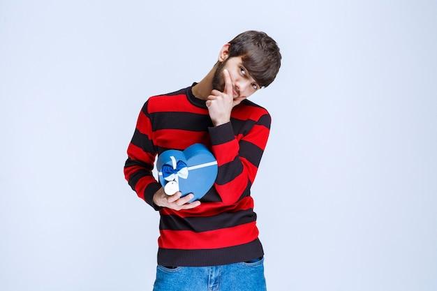 Мужчина в красной полосатой рубашке держит синюю подарочную коробку в форме сердца и выглядит задумчивым или таким, как будто у него есть хорошая идея.
