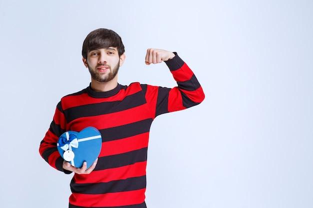 Человек в красной полосатой рубашке держит синюю подарочную коробку в форме сердца и показывает кулак.