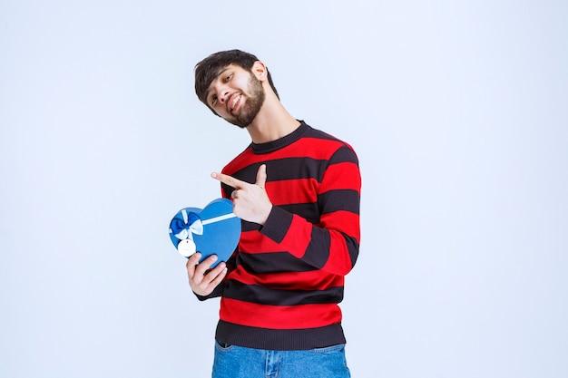 青いハート型のギフトボックスを保持している赤い縞模様のシャツの男。