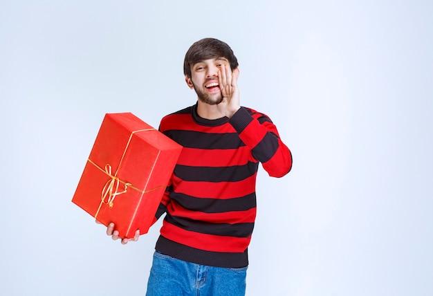 赤いギフトボックスを持って誰かにそれを届けるように呼びかける赤い縞模様のシャツを着た男。