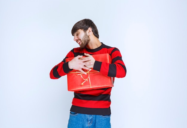 Мужчина в красной полосатой рубашке держит красную подарочную коробку, крепко ее обнимает и не хочет ни с кем делиться.