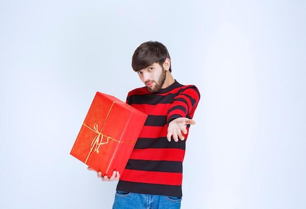 빨간색 선물 상자를 들고 빨간색 줄무늬 셔츠에 남자가 혼란스럽고 사려 깊습니다.