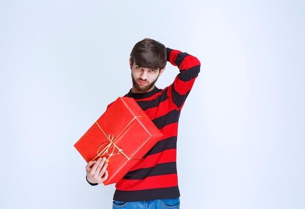 赤いギフトボックスを持っている赤い縞模様のシャツを着た男は、混乱して思慮深く見えます。
