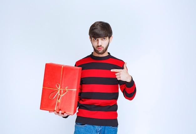 빨간색 선물 상자를 들고 그것을 홍보하는 빨간색 줄무늬 셔츠에 남자.