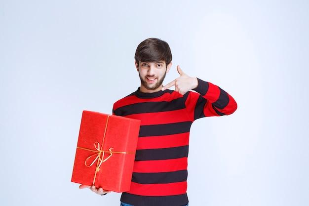 赤いギフトボックスを保持し、それを宣伝する赤い縞模様のシャツの男。