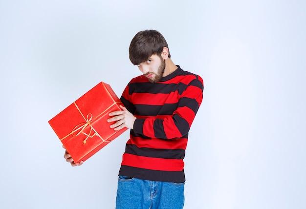 Мужчина в красной полосатой рубашке держит красную подарочную коробку, доставляет и преподносит ее покупателю или своей девушке.