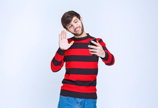 Человек в красной полосатой рубашке держит телефон и делает селфи в энергичных позах.